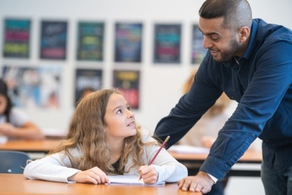 Teacher helping elementary student in class, photo by Fly View Productions/Getty Images