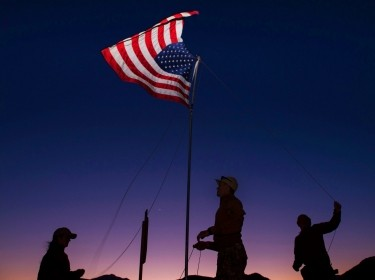 U.S. servicemembers raise a flag