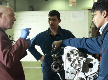 Teacher helping students with a car engine
