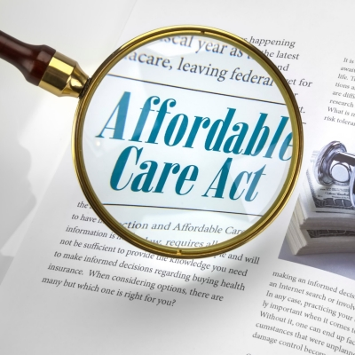 "Magnifying glass over ""Affordable Care Act"" text"