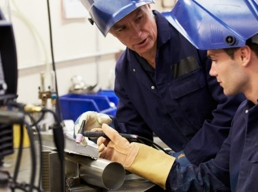 Engineer teaching apprentice to use a welding machine