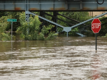A flooded road with a stop sign visible above the flood water and a railbridge in the background, photo by CHRISsadowski / Getty Images