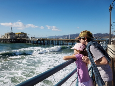 Two children looking at the ocean with Santa Monica pier in the background