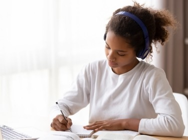 Serious African American teenage girl wearing headphones, doing homework, photo by fizkes/AdobeStock