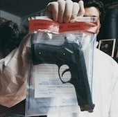 forensic scientist holding gun in evidence bag