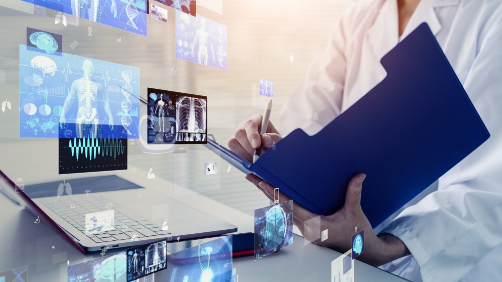 Health information technology symbols in front of a doctor with an open laptop and clipboard, photo by metamorworks/Getty Images