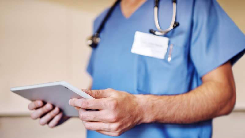 Doctor using a tablet with stethoscope and ID badge around his neck, photo by PeopleImages/Getty Images