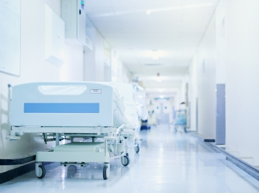 Hospital bed in a hospital corridor, photo by PeopleImages/Getty Images