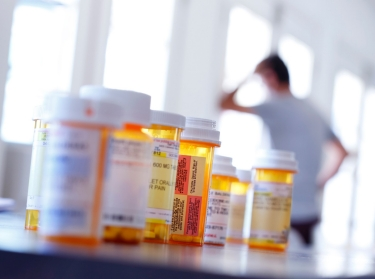 Prescription pill bottles on a table in the foreground with a man in the background, leaning against the wall