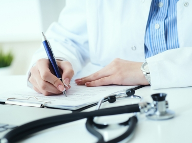 Close up of a doctor writing on a clipboard, photo by Cameravit/Getty Images