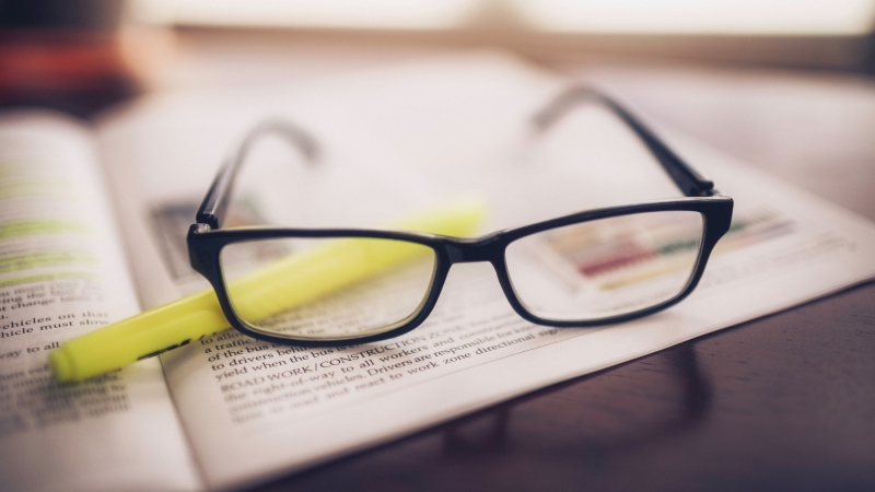 Glasses and yellow highlighter on top of a magazine