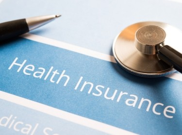 Pen and stethoscope on health insurance papers