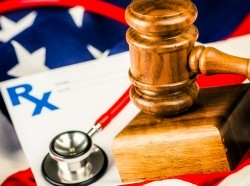 Prescription pad, stethoscope, and gavel on top of the American flag