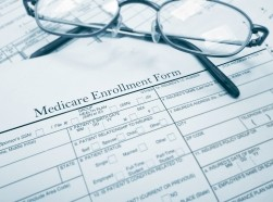 A pair of glasses on top of a Medicare enrollment form, photo by zimmytws/Getty Images