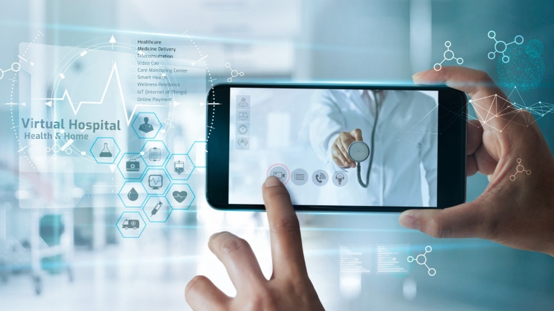 """Hand holding a smartphone with a doctor on screen and """"virtual hospital"""" in the background, photo by ipopba/Getty Images"""