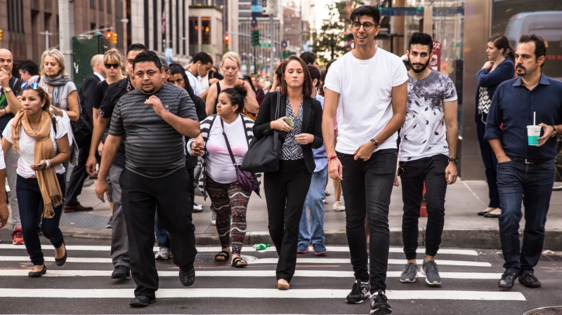 New York City, New York, USA - September 14, 2015: A crosswalk in midtown Manhattan with with a diversity of pedestrians crossing.