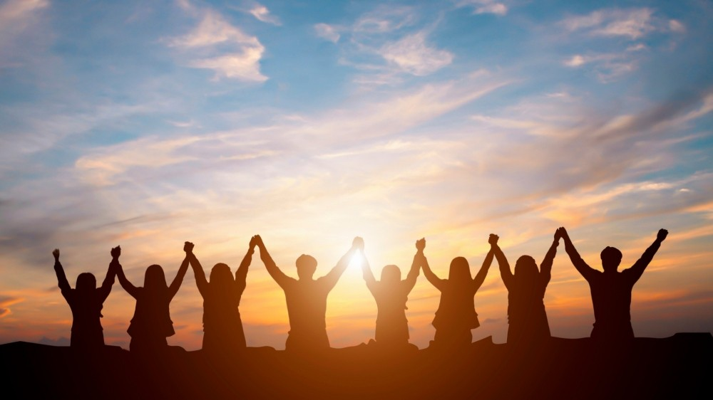 Silhouette of a group of people holding hands and raising their arms in front of the sunset, photo by Moostocker/Getty Images