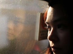 Close up of a woman looking out a window, photo by Lewis Tse Pui Lung/Adobe Stock