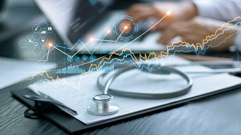 Graph icons superimposed over a clipboard with a stethoscope on it and a person typing on a laptop in the background, photo by ipopba/Getty Images