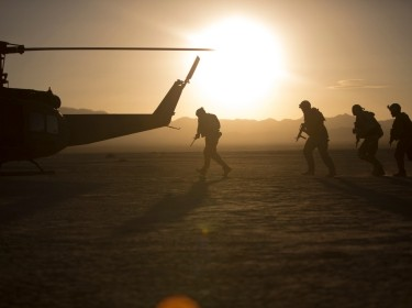 Soldiers boarding helicopter in the desert with the sun setting in the background