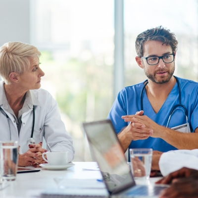 Group of doctors sitting around a table having a discussion