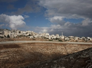 A section of the Israeli barrier cuts beneath the West Bank refugee camp of Shuafat, October 31, 2014
