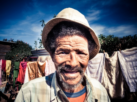 adult,africa,african,aged,aging,alone,background,beard,black,day,elderly,expression,eyes,face,friendly,grey,guy,hair,happy,hat,human,joy,life,male,man,old,outdoor,person,poor,poverty,rural,senior,shirt,smile,toothless,vibrant,wrinkles