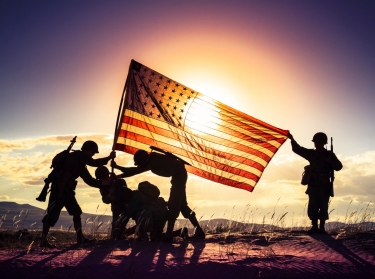Soldiers in silhouette raising the American flag