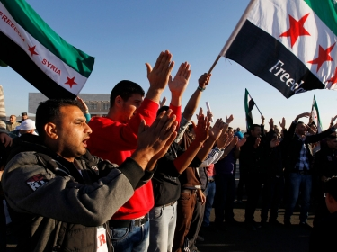 Syrian refugees wave flags during a protest against Syria's President Bashar al-Assad