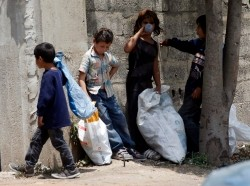Syrian refugee children collect plastics as they stand along a street in southern Lebanon