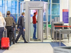 Passengers wait to enter the xray machine as a man is scanned at an airport,