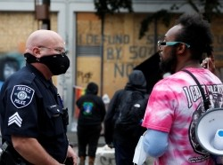 Seattle Police officer Robert Brown talks with protesters as other officers collect evidence at the CHOP (Capitol Hill Organized Protest) area after a fatal shooting as people occupy space in the aftermath of the death in Minneapolis police custody of George Floyd, in Seattle, Washington, U.S. June 29, 2020.