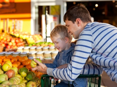 father and son shopping for produce