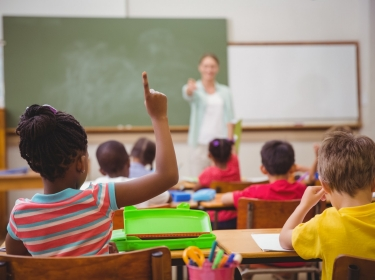 Student raising her hand during class