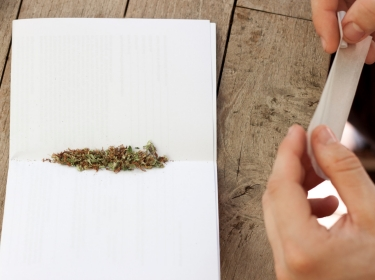 Hands holding rolling paper and filter over a table with a mix of marijuana and tobacco on white paper