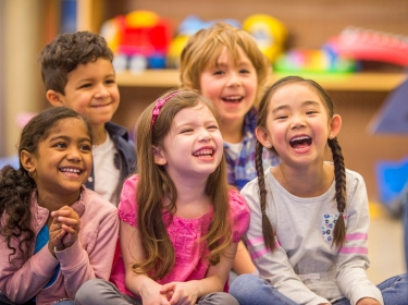 Preschool-age children laugh while their teacher reads them a book during story time