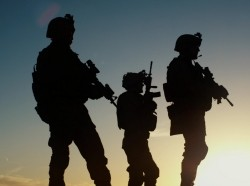 Soldiers in military gear are silhouetted against the setting sun.