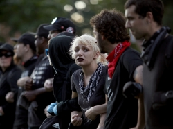 """Protesters with a group known as """"Antifa"""", or anti-fascists, link arms at an event on the campus of the University of Virginia organized by the group Students Act Against White Supremacy marking the one year anniversary of a deadly clash between white supremacists and counter protesters August 11, 2018 in Charlottesville, Virginia."""