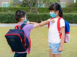 Two children wearing backpacks bump elbows as a greeting during the COVID-19 pandemic, photo by ake1150sb/Getty Images
