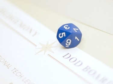 A blue die sits atop a rule sheet for Hedgemony during a demonstration of  gameplay.