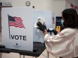 Election worker Gisela Alberg cleans a voting booth at Sonoma Elementary School during the primary election in Las Cruces, New Mexico, U.S., June 2, 2020, photo by Paul Ratje/Reuters
