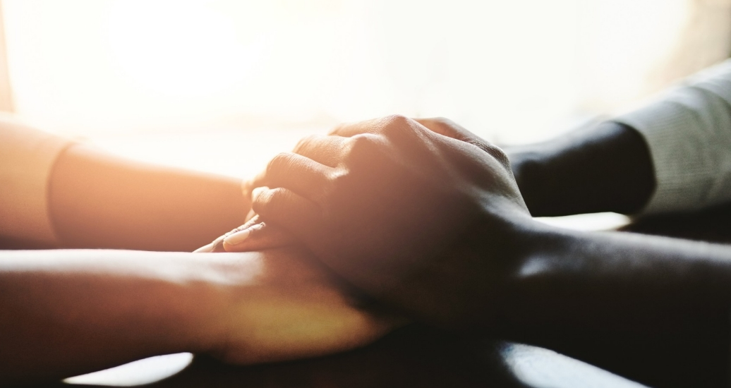Closeup shot of two people holding hands in comfort.