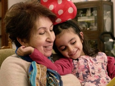 A young girl reading with her grandmother, photo by Malek Hosni