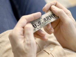 """A closeup photograph of a pair of hands holding a """"U.S. Army"""" patch, photo by Synthetic-Exposition/Getty Images"""