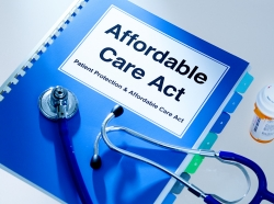 Manual handbook for the Patient Protection and Affordable Care Act with a stethoscope and prescription medication bottle