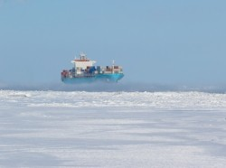 Large cargo filled with containers navigating through ice surrounded passage, photo by Jean Landry/Getty Images