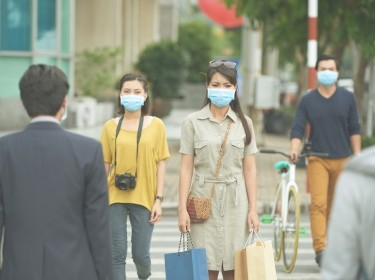 People crossing a street wearing face masks, photo by DragonImages/Getty Images