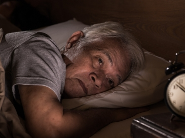 Man lying in bed staring at the clok, photo by amenic181/Getty Images