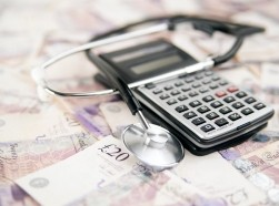 Calculator and stethoscope on top of UK money, Photo by ljubaphoto/Getty Images