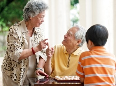 Grandparents teaching their grandson how to play Xiangqi, Chinese chess